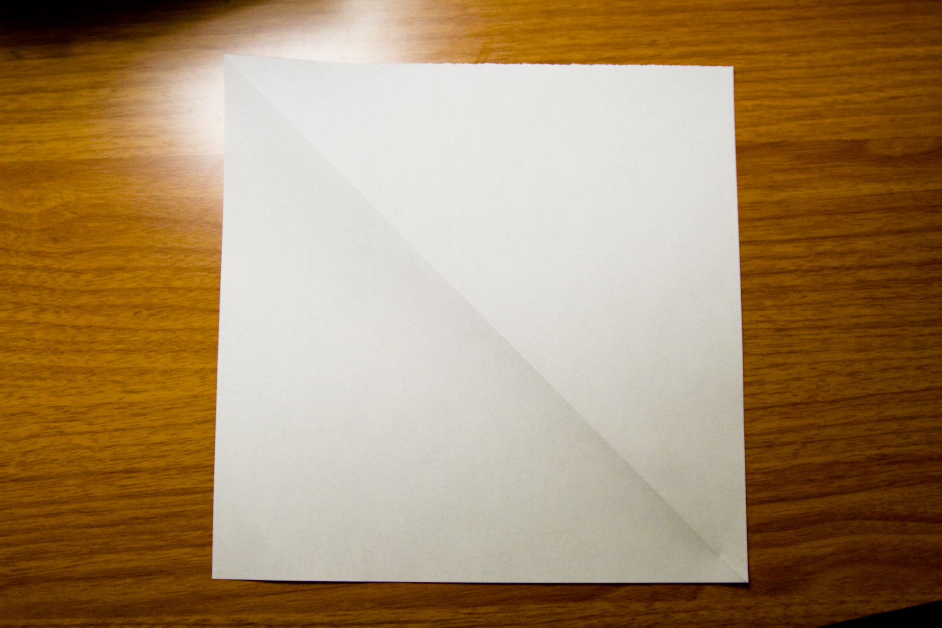 A square piece of paper on a wooden table.