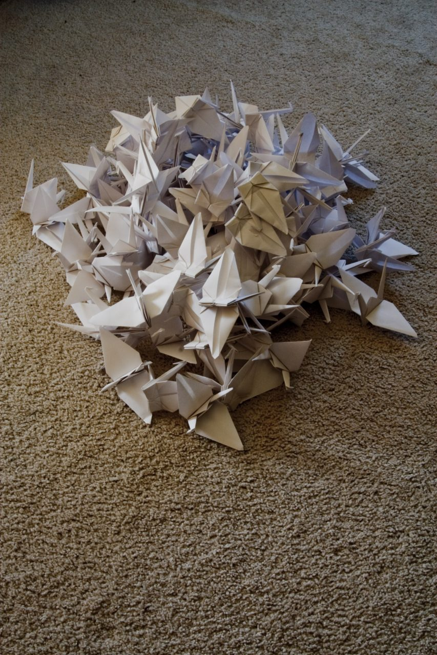 A pile of 100 paper cranes sitting on a carpet