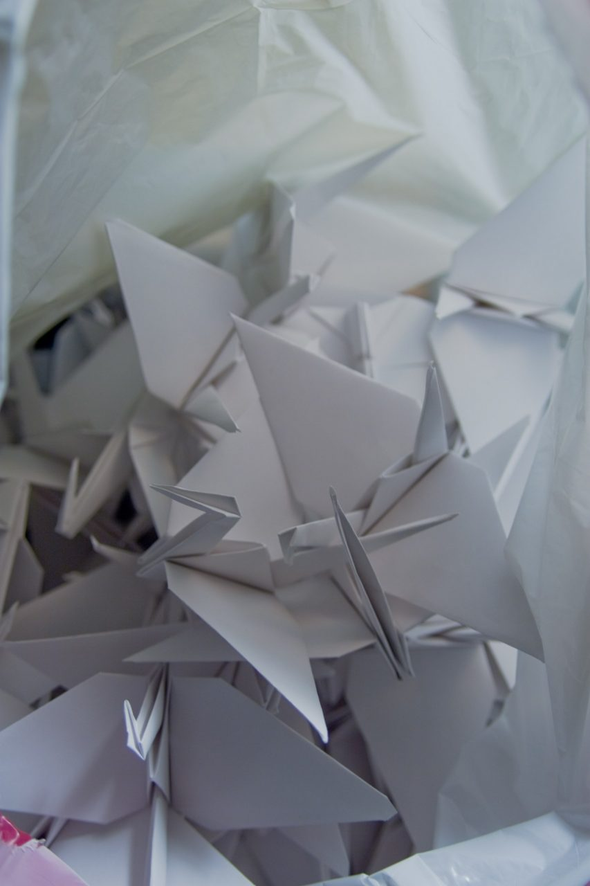 A pile of white paper cranes in a white plastic bag.