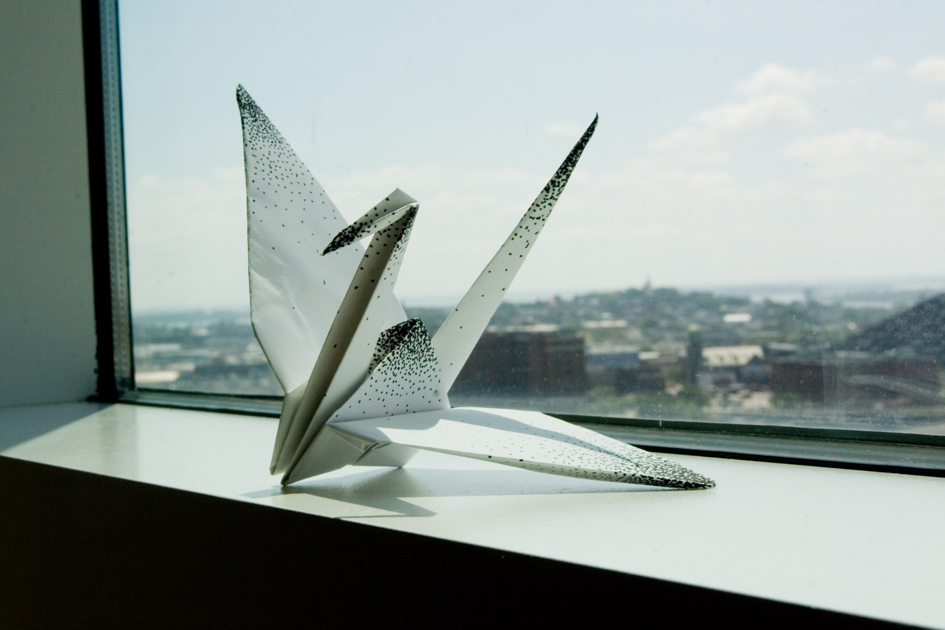 A paper crane with polka dots sitting on a window sill