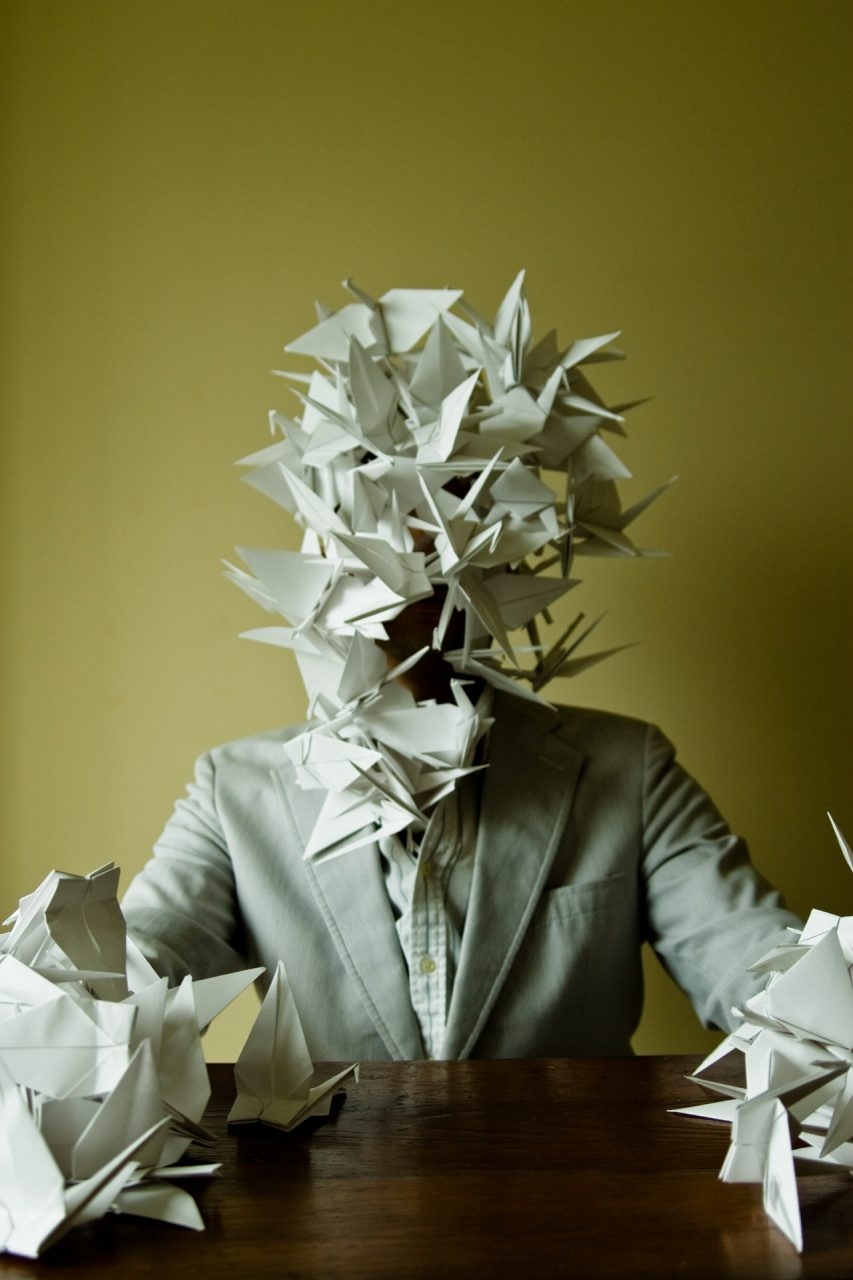 A suit sitting at a desk with hands and face covered in paper cranes.