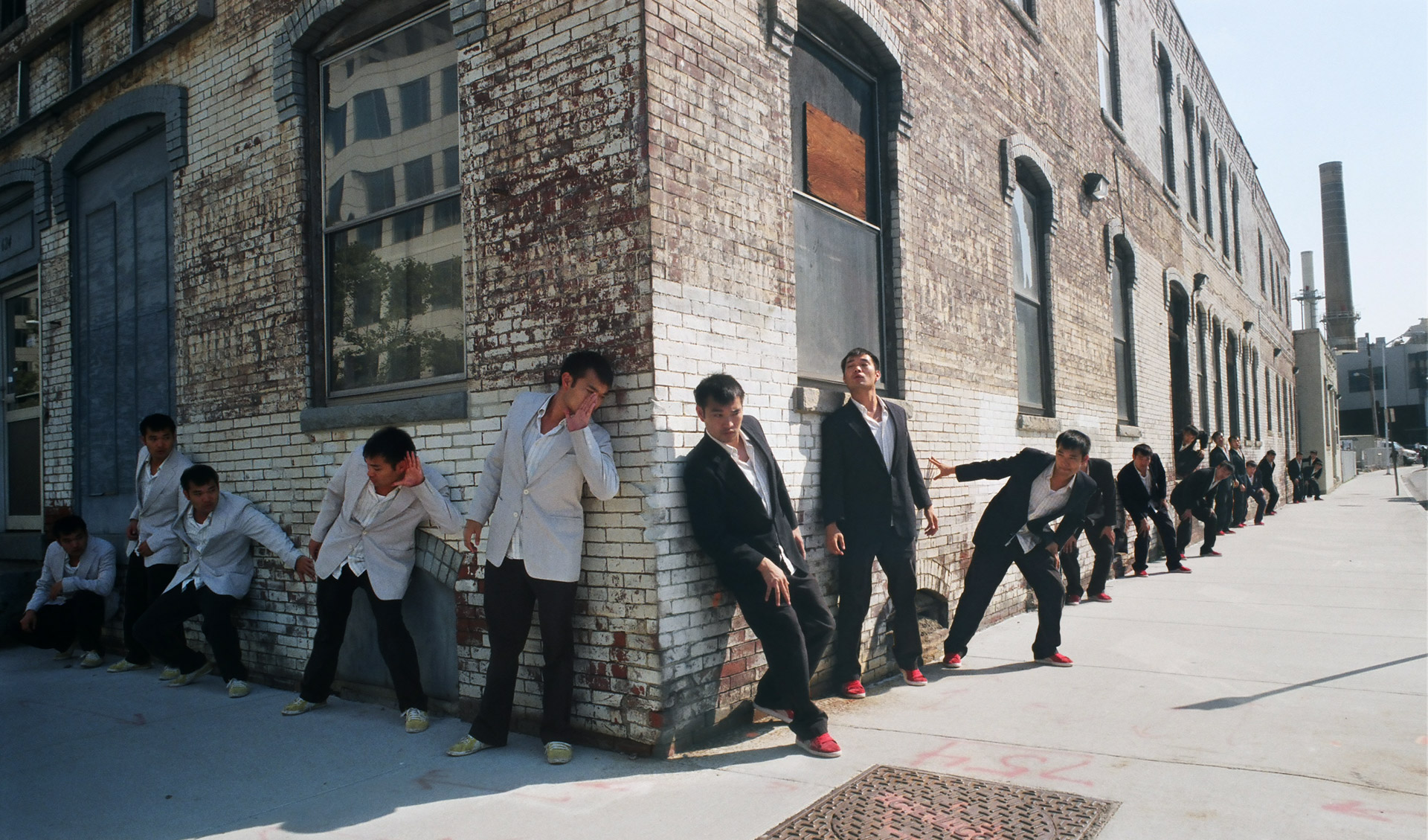 Two groups of asian guys on a corner. One in dark suits, one in white suits with the two members at the corner whispering to each other and everyone else trying to listen in.