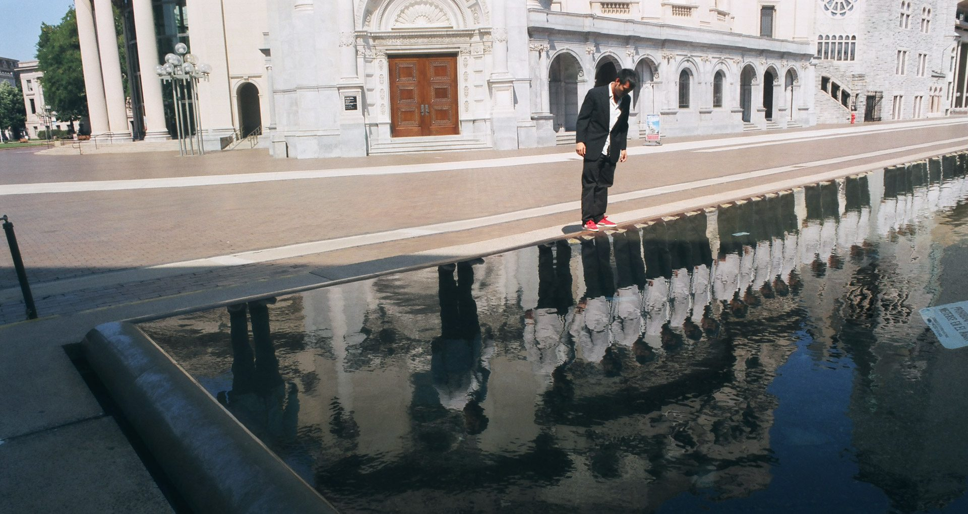 A man in a dark suit standing in front of a reflecting pool, a line of same man in white suits reflected back.