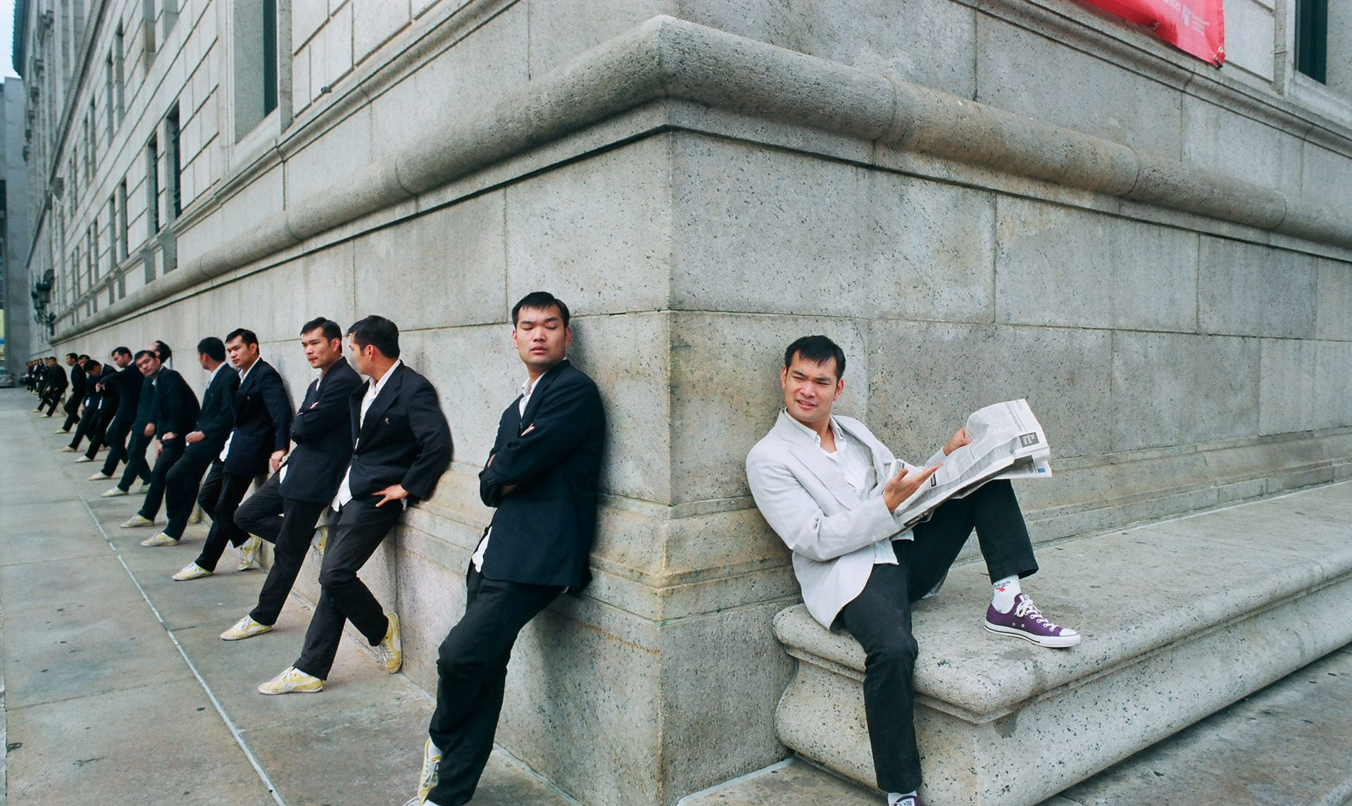 An Asian man in white reading a newspaper on a corner, a line of the same Asian man in black looking bored around the corner.