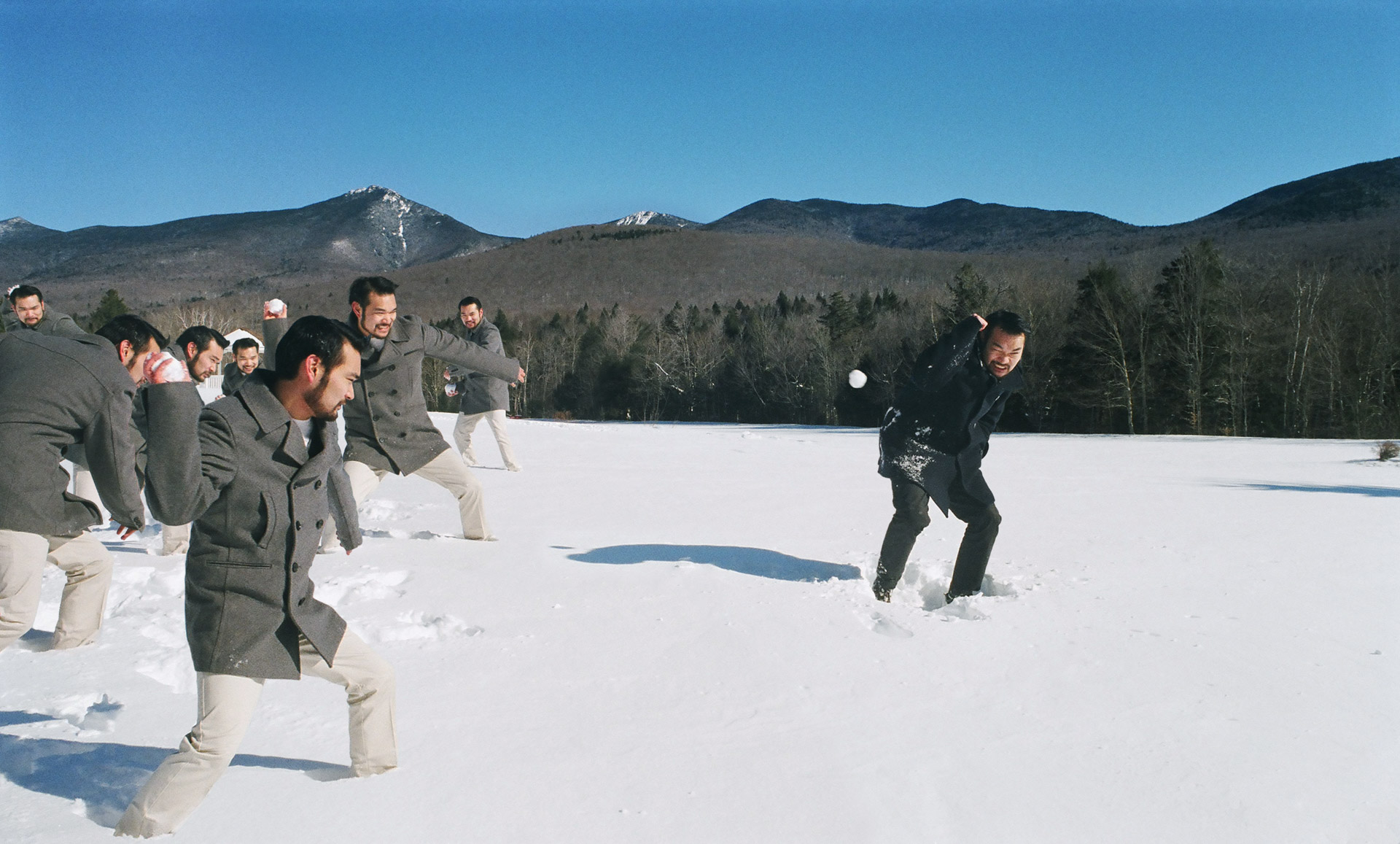 A guy in white throwing snowballs at the same guy in black.
