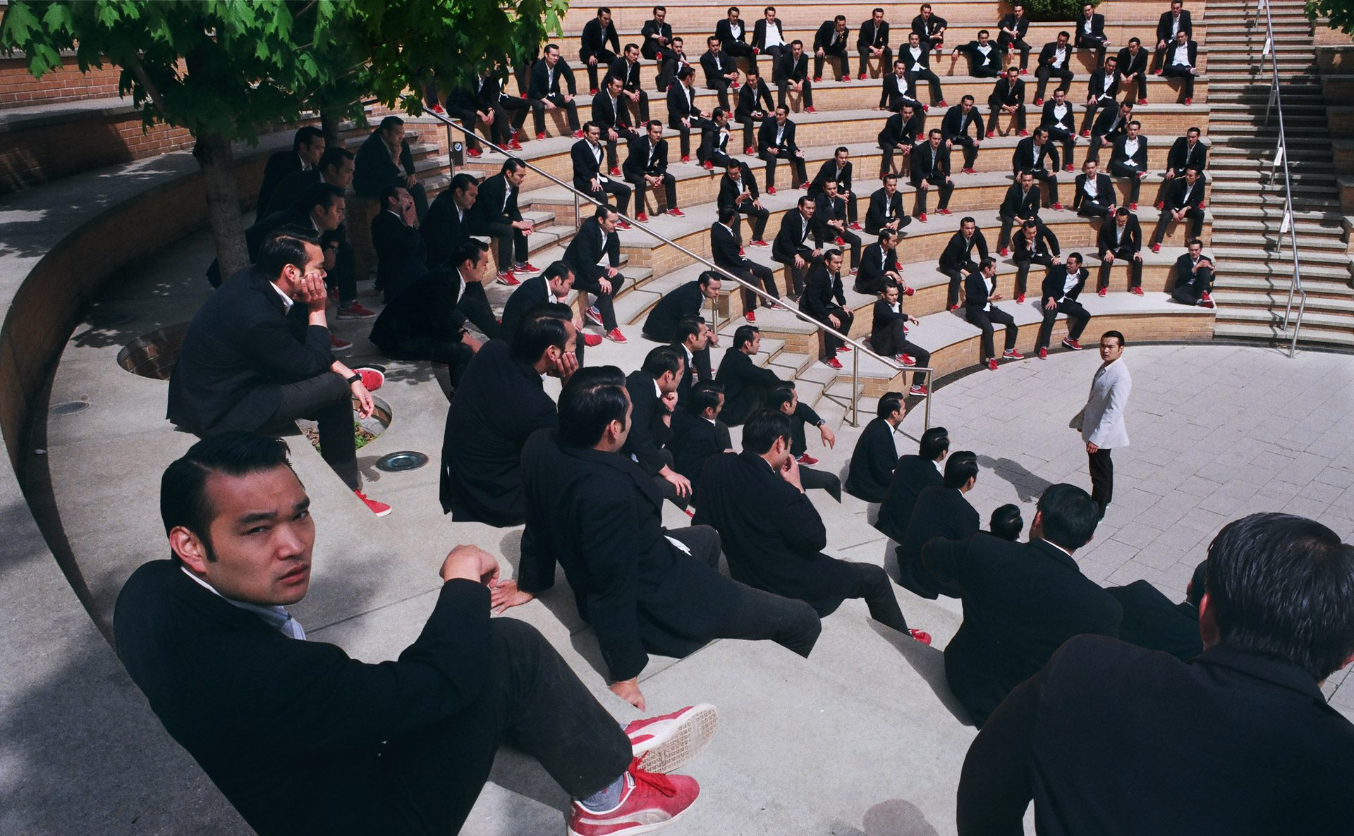 Amphitheater full of asians in dark suits, with the same asian in white standing in the center looking into the camera.
