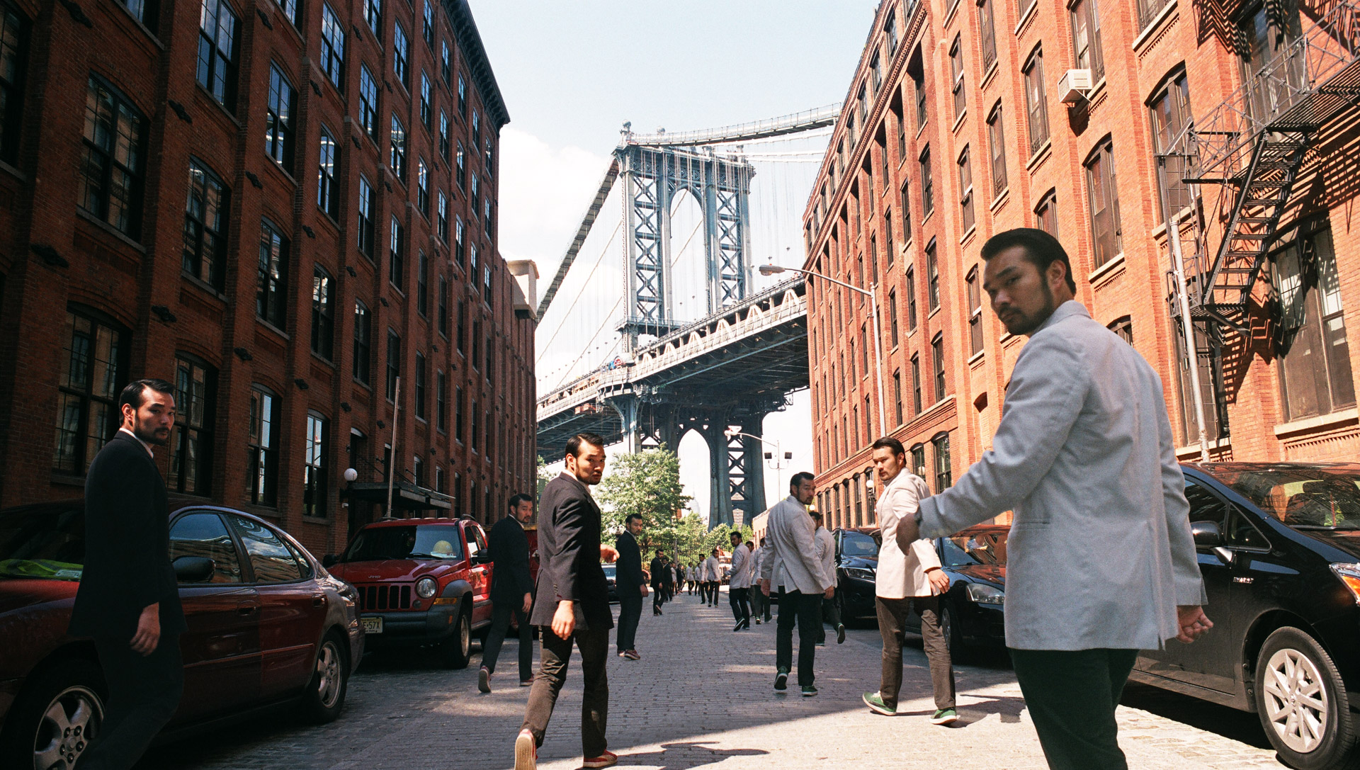 Three lines of Asian men in black and white suits walking towards the Manhattan bridge in DUMBO.