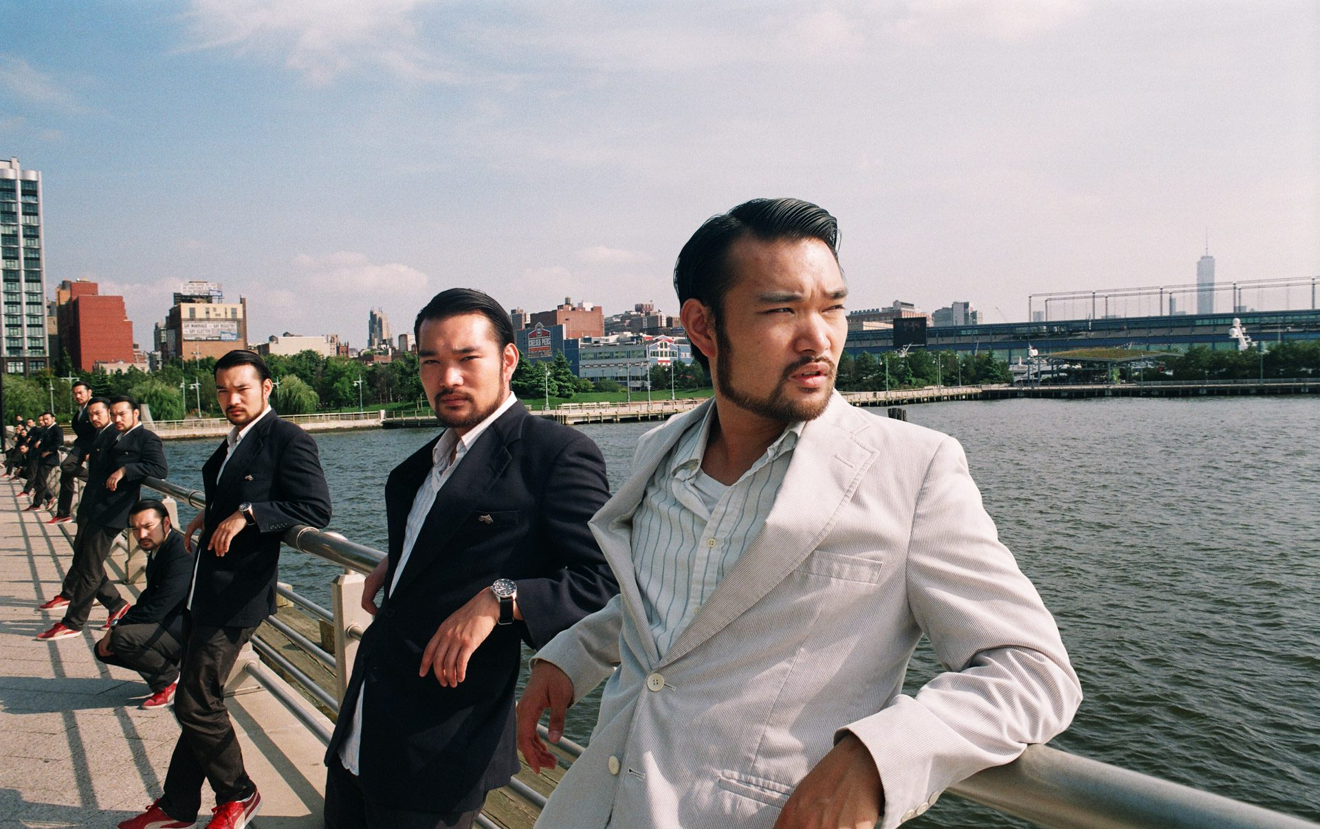 A group of asian men in dark suits looking at the camera, same asian in a white jacket looking away.