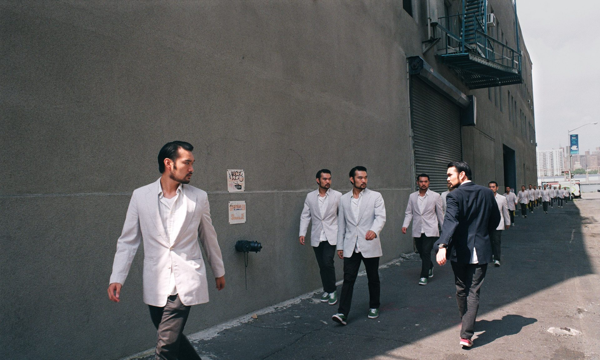 A group of asians in white suits walking one way, staring at the same asian in a dark suit walking the other way.
