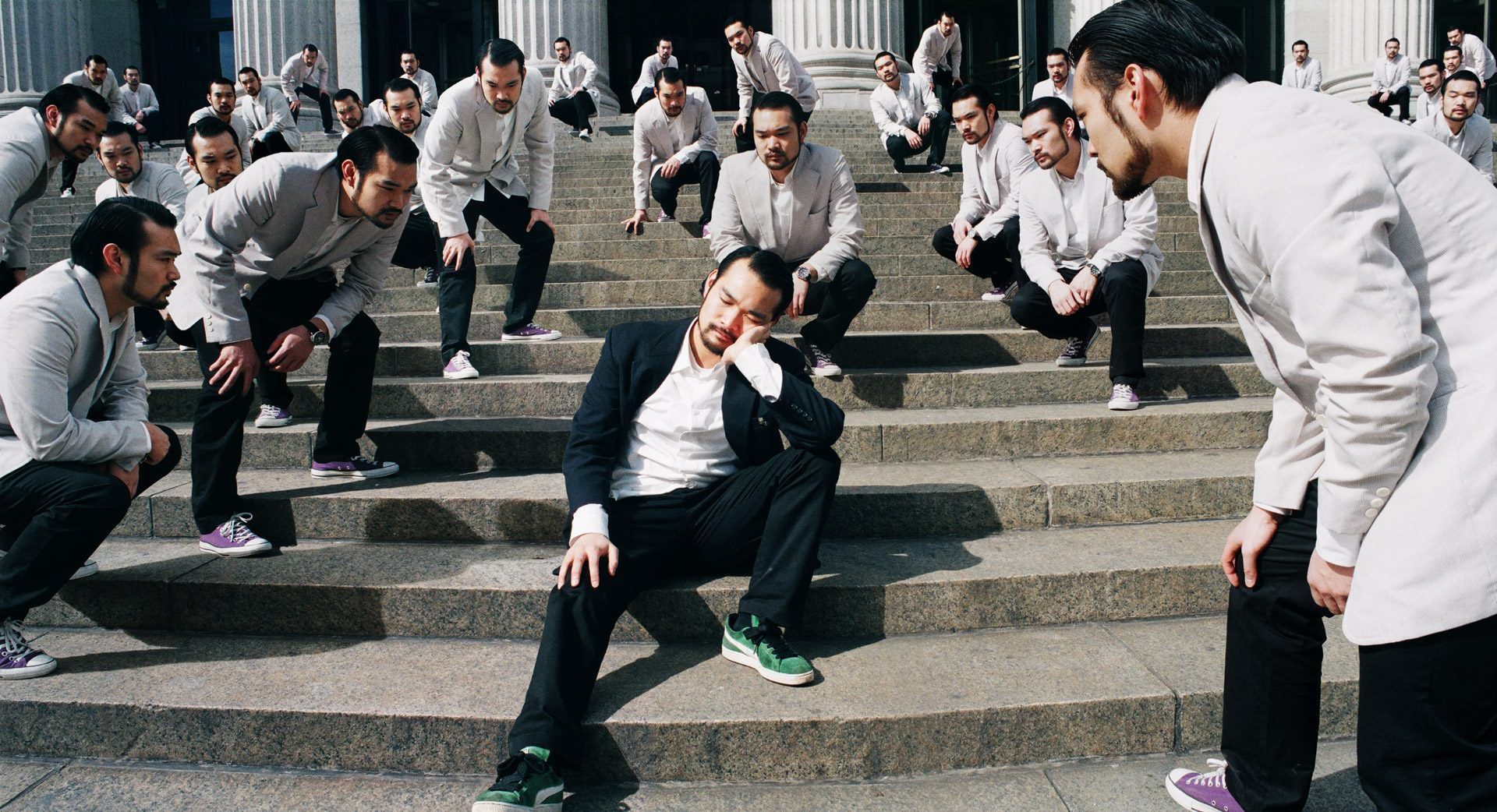 An asian in a dark suit sleeping on some steps, same group of asians in white suits staring at him.
