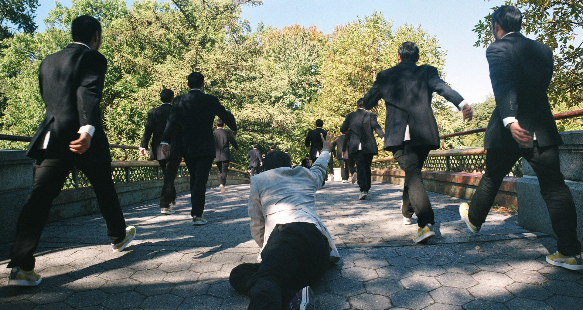 One asian in a white suit on the ground reaching out, a group of asians in dark suits walking past him.