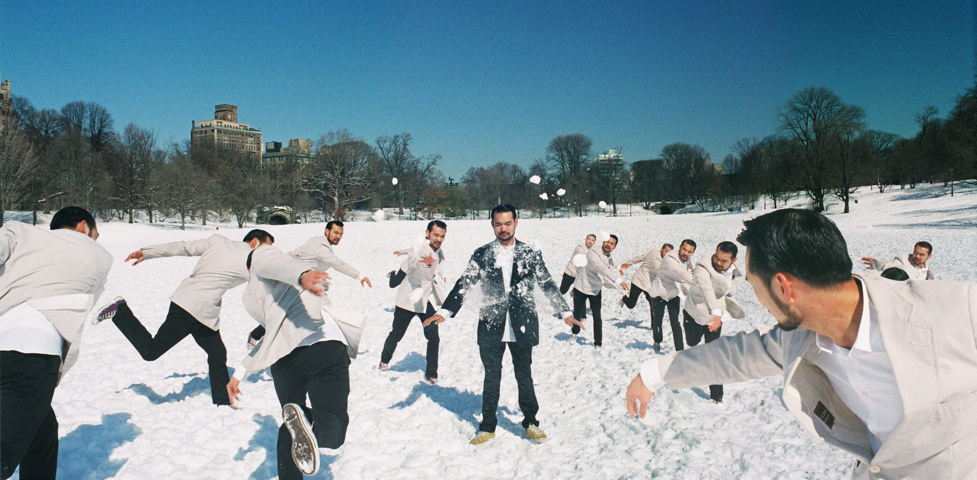 A group of asians in white suits throwing snowballs at the same asian in a dark suit getting hit.
