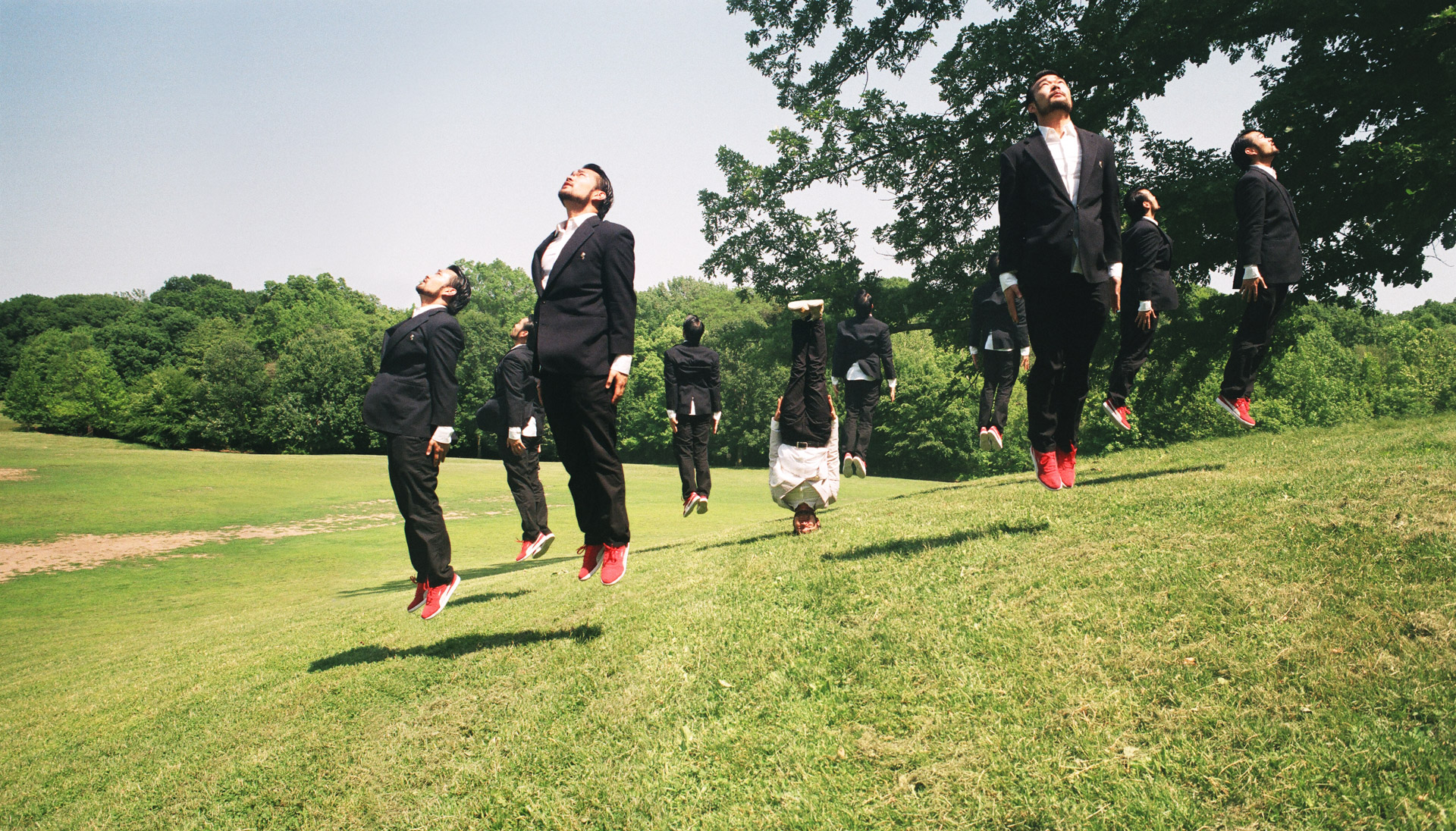 A circle of Asians in the dark suits jumping straight up, with an asian in a white suit standing on his head in the center.