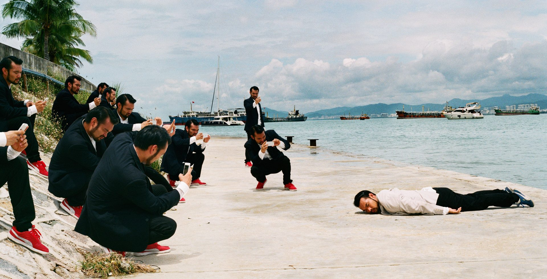 An asian in white lying face down on the ground next to the ocean, same group of asians in black taking pictures of him.