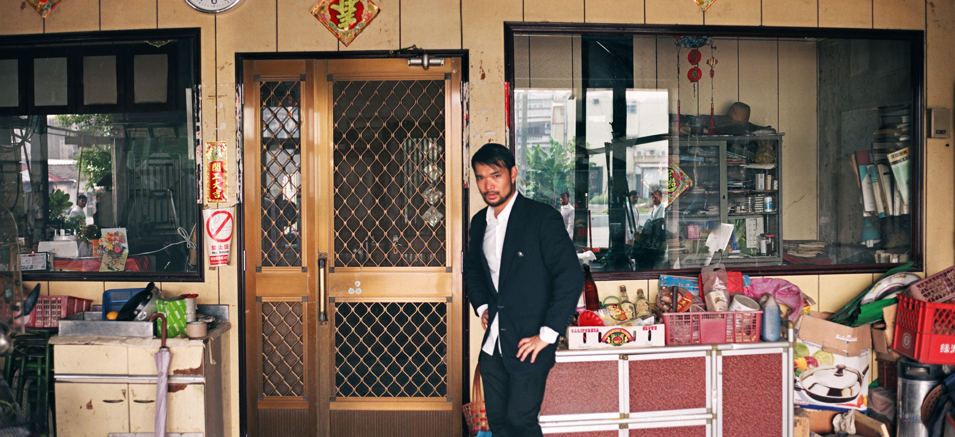 A very sweaty asian in a dark suit, standing next to two windows with the same asian in a white suit walking past in the reflection.