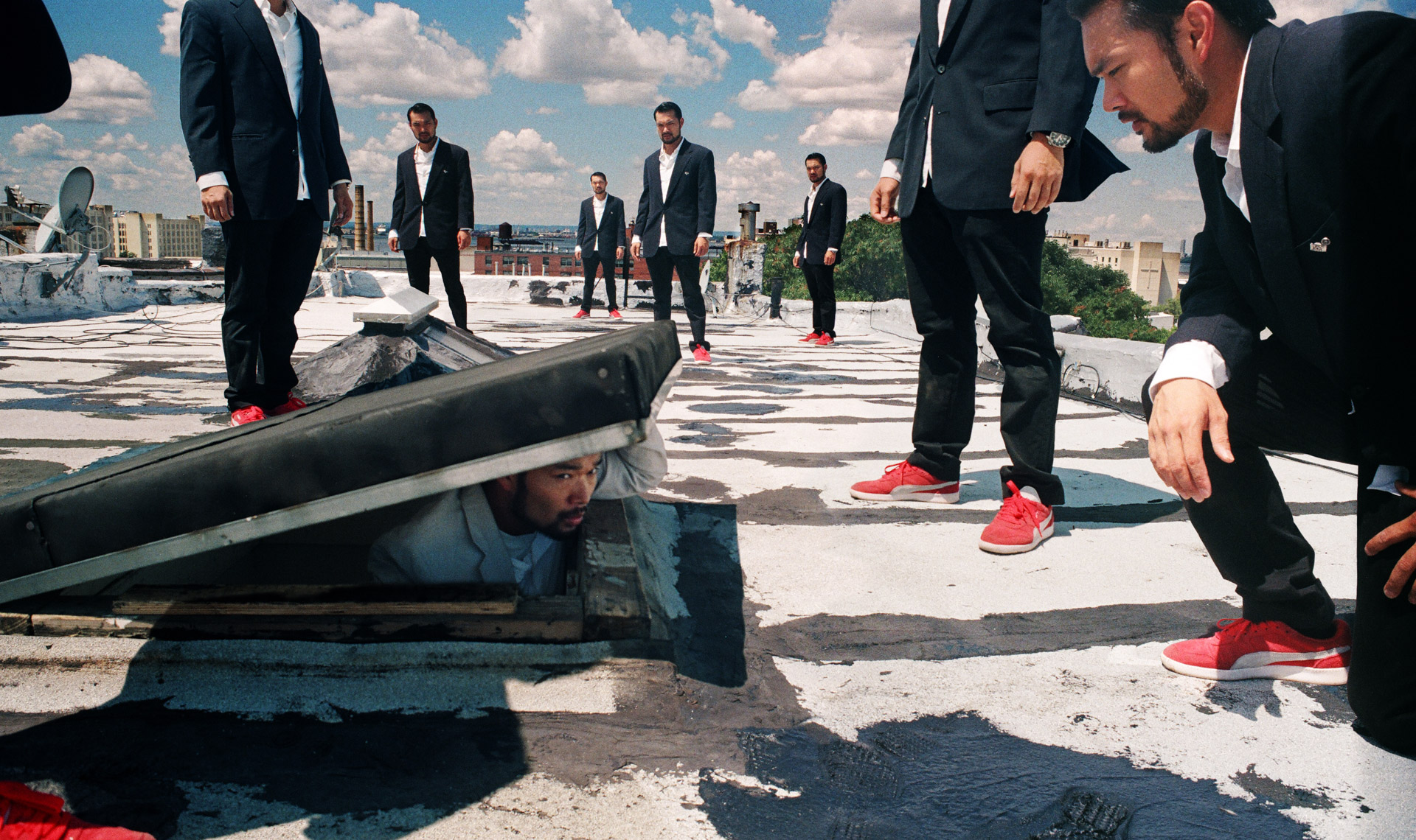 An asian in a white suit looking out from a rooftop manhole. A group of the same asian standing on the roof looking at him.