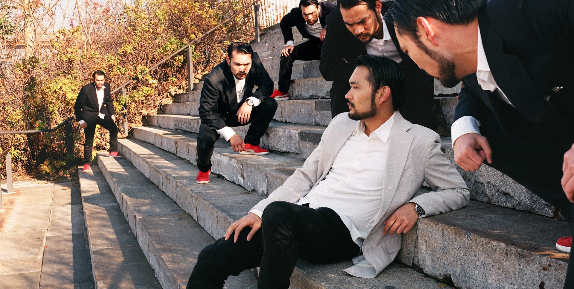 A group of asians in dark suits, staring at the same relaxed asian in a white suit.