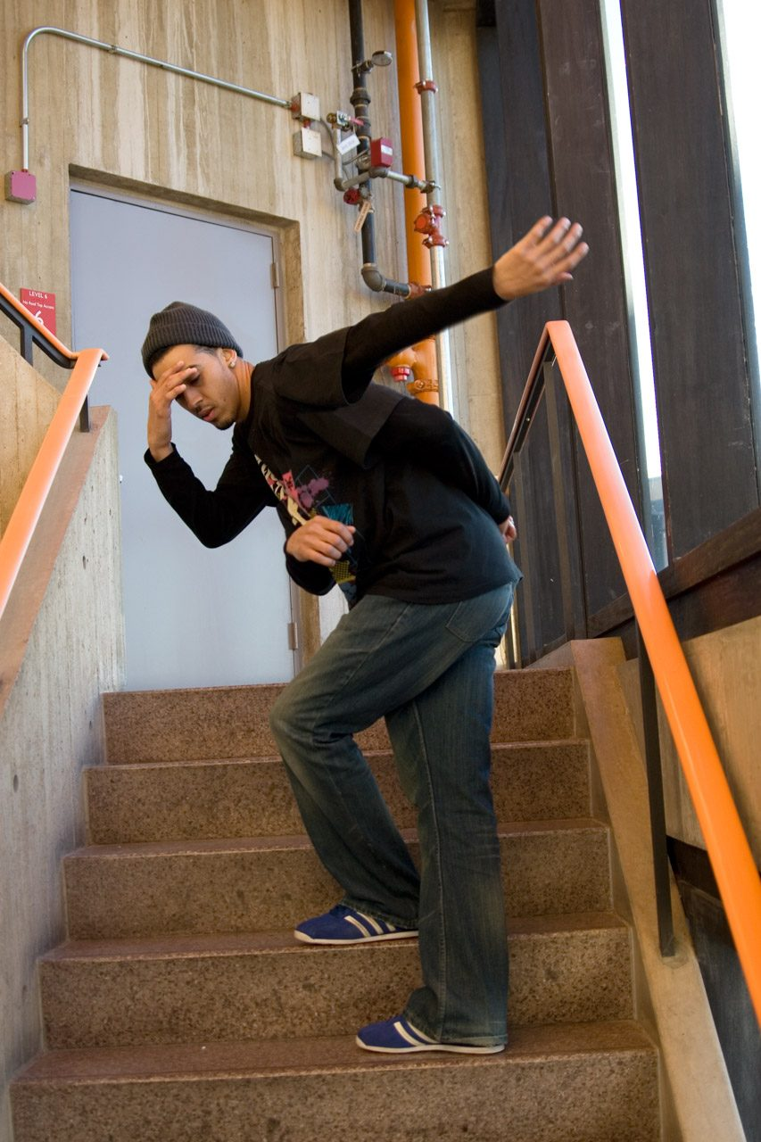 A dancer on the stairs with two extra arms.