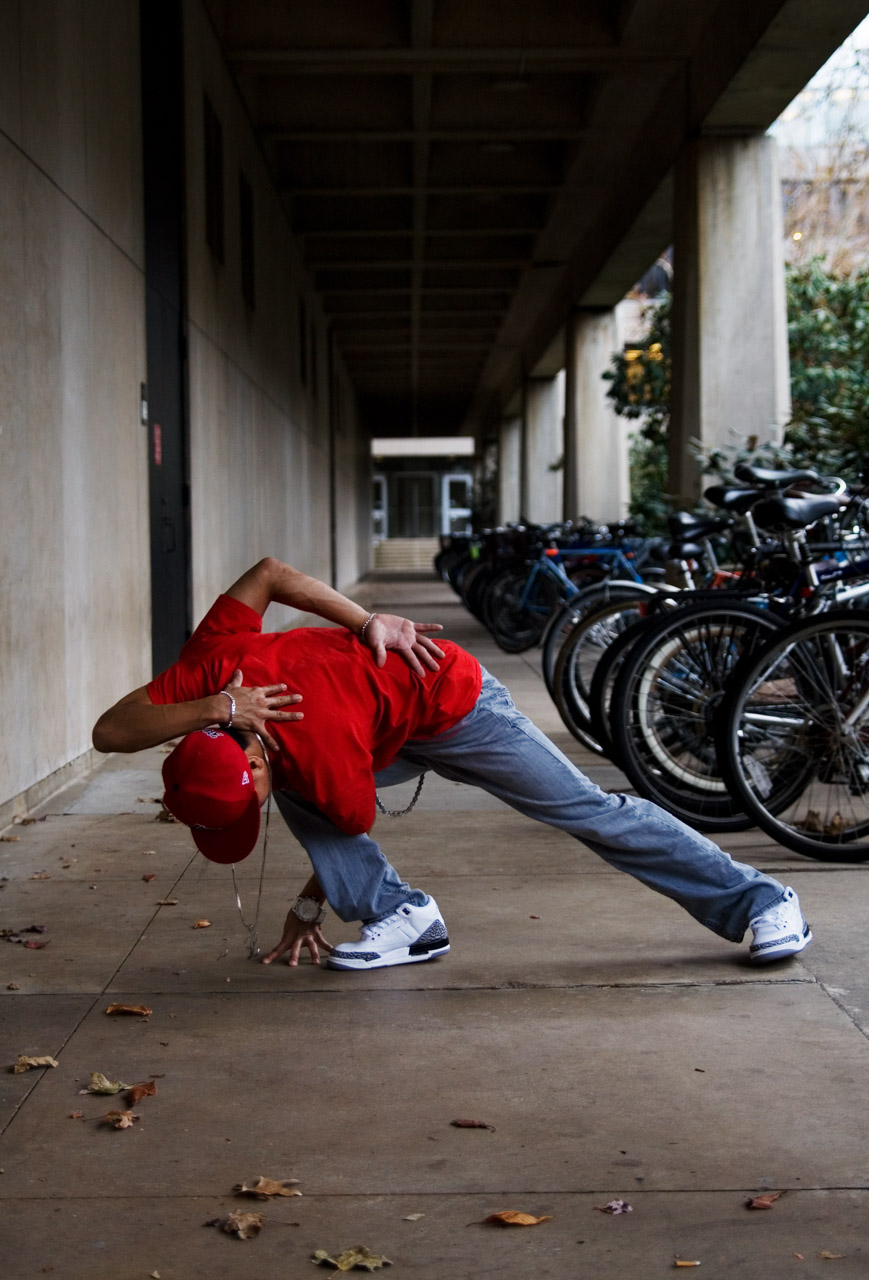 A dancer in red, posing on the ground with an extra arm on his back.