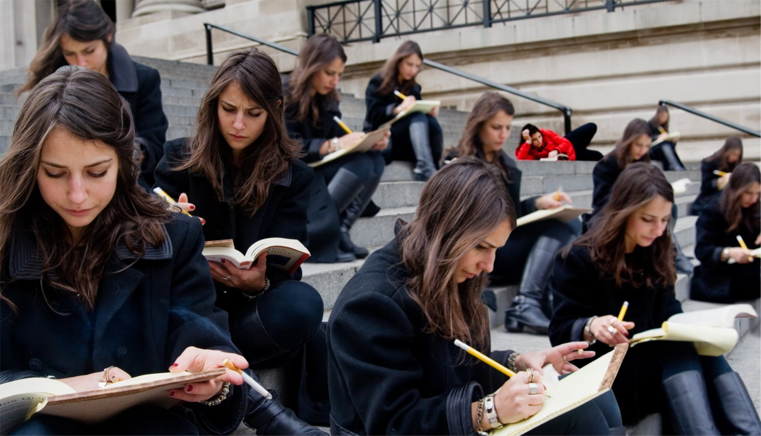 Group of women with brown hair and dark jackets reading and taking notes on the front steps of the Metropolitan Museum of Art. One women in the background in red reading lazily on her side.