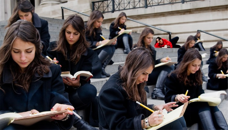Group of women with brown hair and dark jackets reading and taking notes on the front steps of the Metropolitan Museum of Art. One women in red in the background reading on her side, laying lazily.