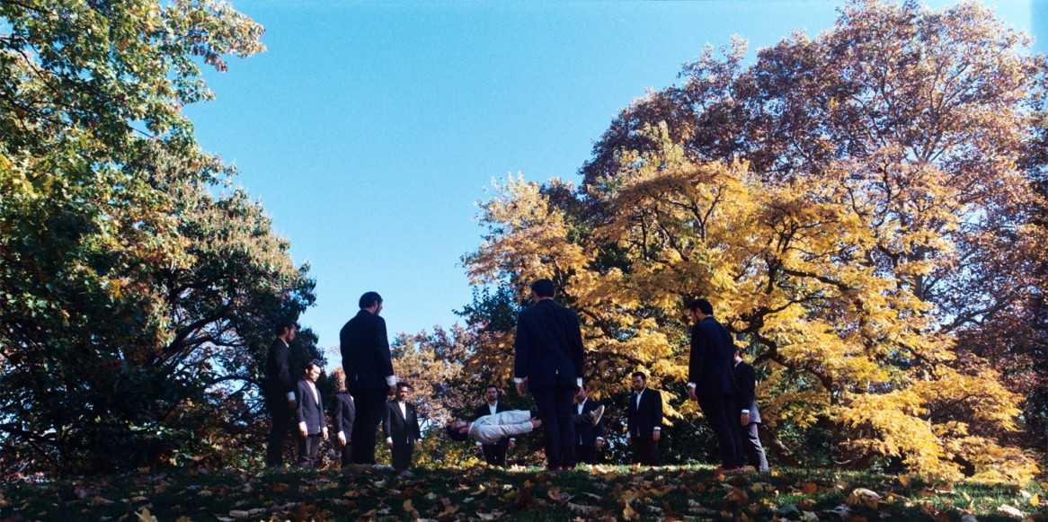 A group of Asian gentleman standing in a circle on a hill, with a fall scene in the background. At the center of the circle is an Asian gentleman in white, floating in mid air on his back.