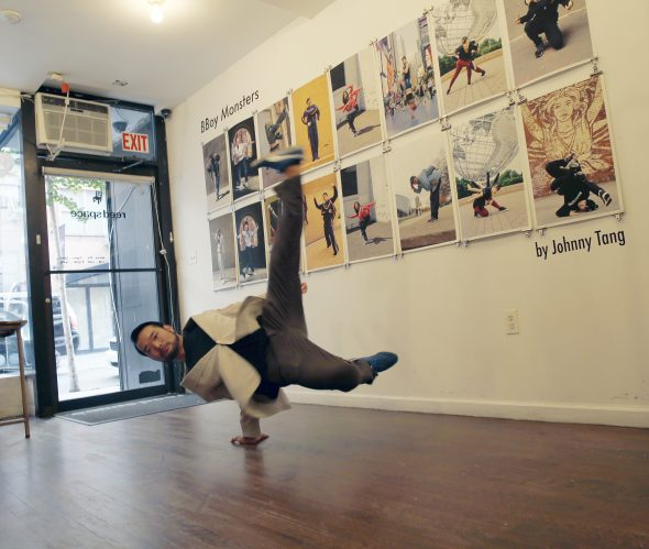 Johnny Tang, artist behind the bboy monsters series posing in front of his works.