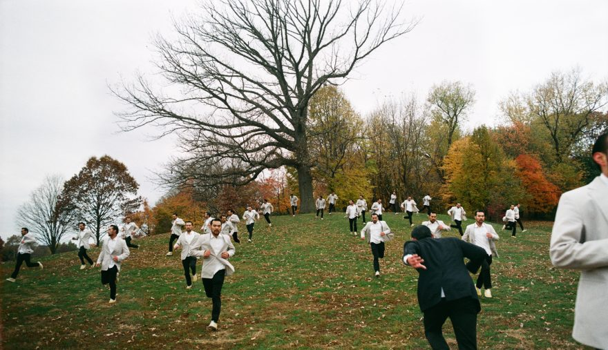 Fearful Courage - white suits running away from foliage woods, a single black suit running towards foliage woods.