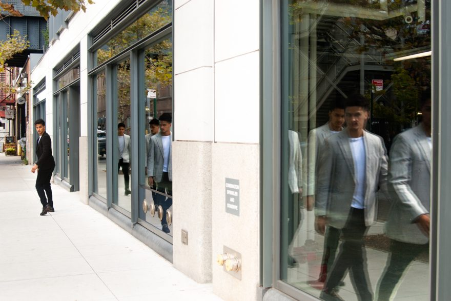 Walking Narcissist - A man in a dark suit walking in the street, with a line of men in white suits reflected in a window, walking in the opposite direction.