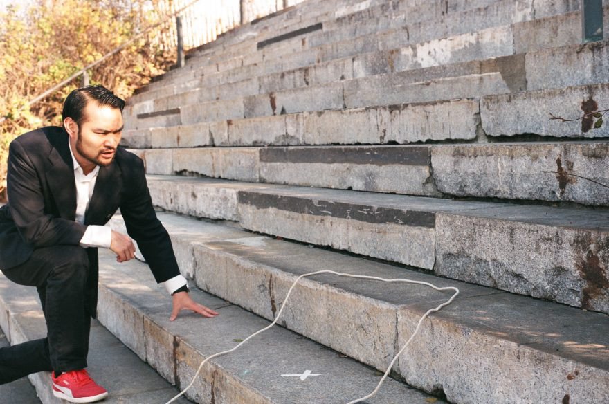 Asian guy angrily looking at an empty rope circle on some steps with a white x in the middle of it.
