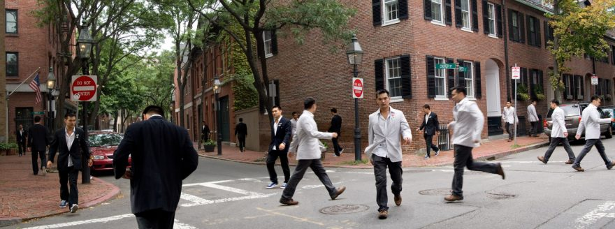 Group of Asian men in dark and light suits crossing the street in Boston.