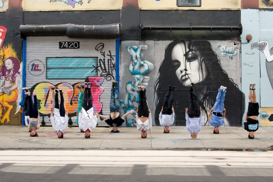 A group of Asian dancers in uniforms, standing on their head next to a graffiti wall at the Five Points in Queens, NY.