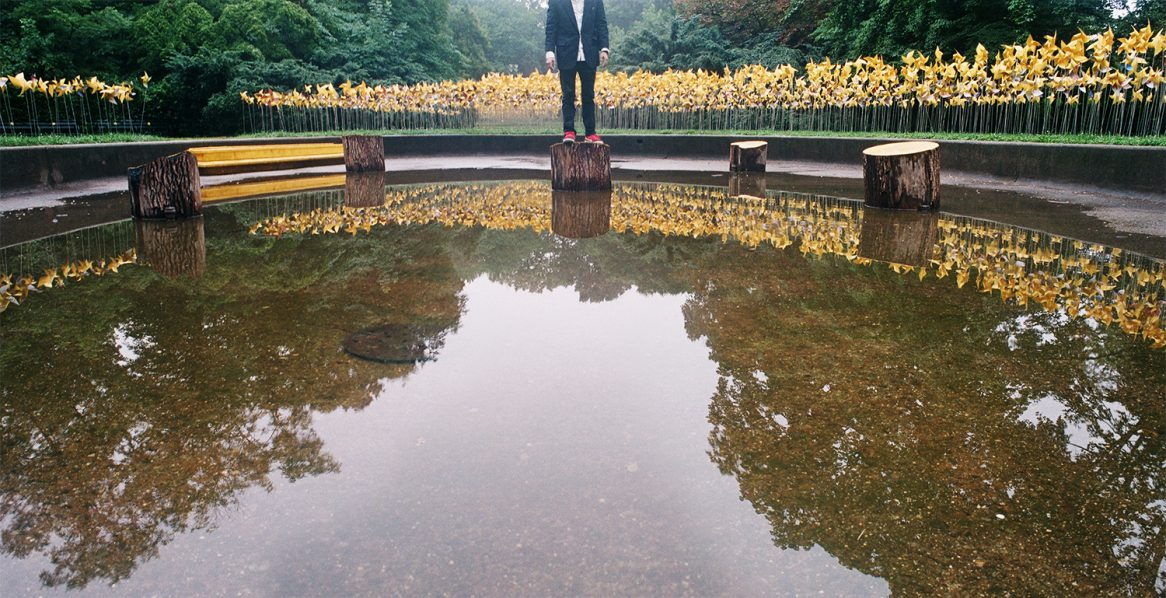 guy in a dark suit standing on a stump in the middle of a big puddle.