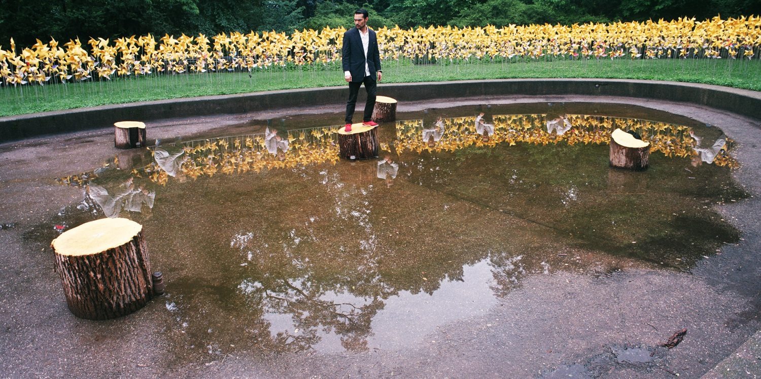 Asian man in black standing on a stump in the middle of a pond, men in white reflected within the pond looking at him.
