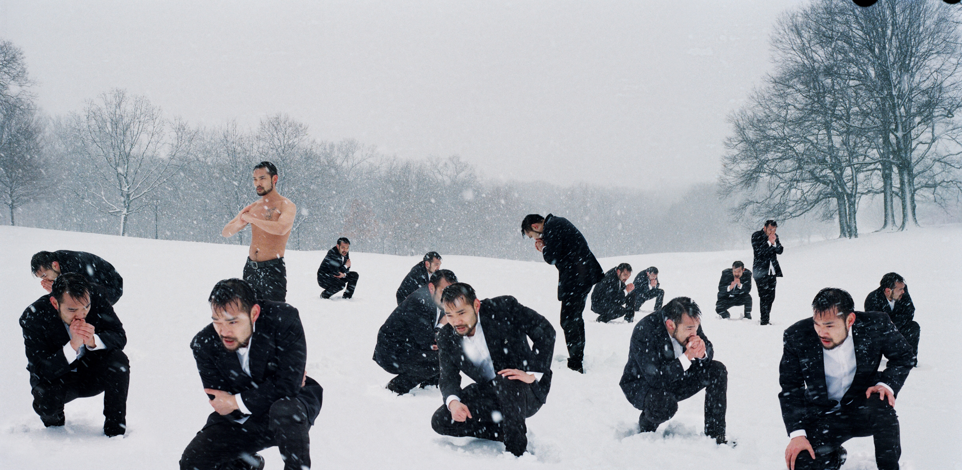 Feeling Numb - A shirtless man standing in a snow storm surrounded by a group of men in black freezing their asses off.