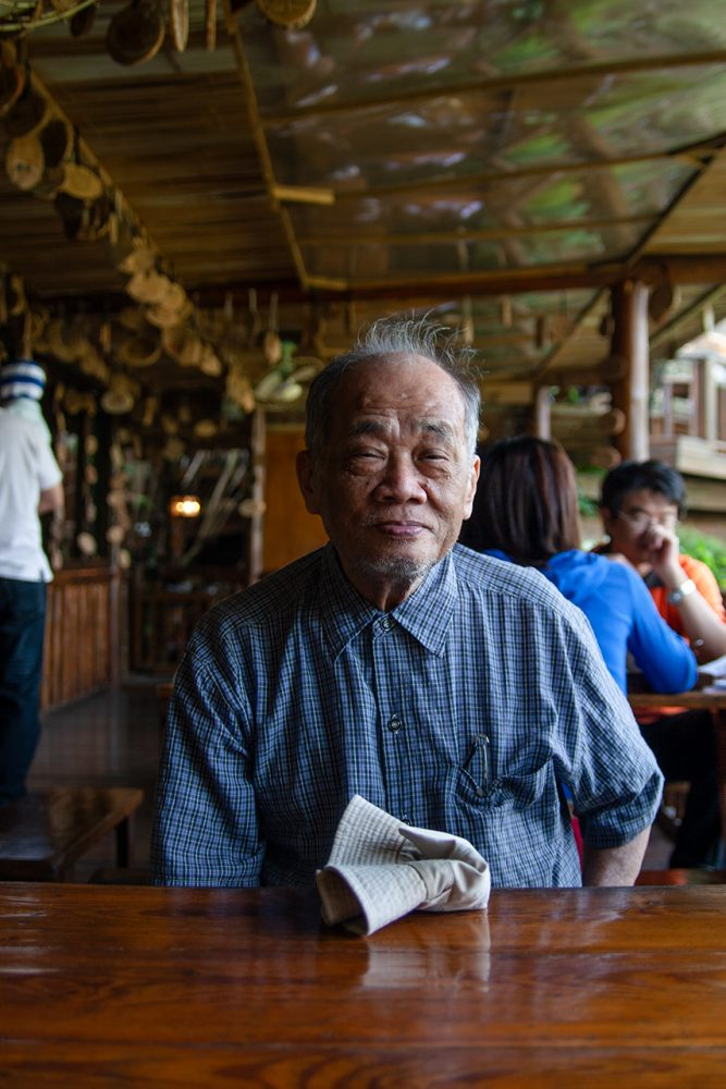 Elderly Taiwanese man sitting at a wooden table smiling.