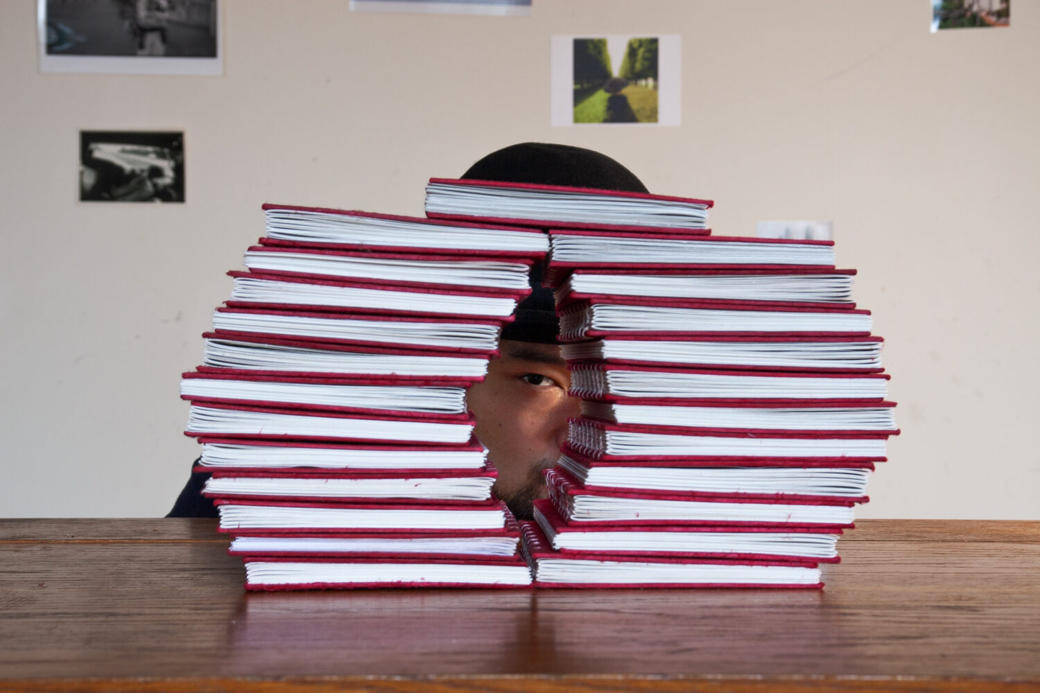 An Asian man in a derby hat peering through a pile of 37 little red books.