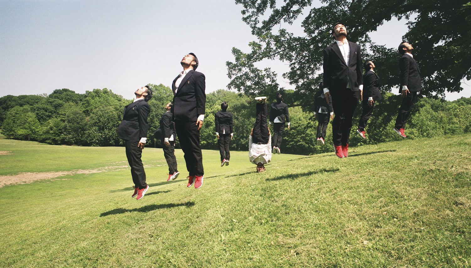 Group of asian men in dark suits jumping straight into the air forming a circle, one asian man in a light colored suit standing on his head in the middle of the group, on a grassy hill.