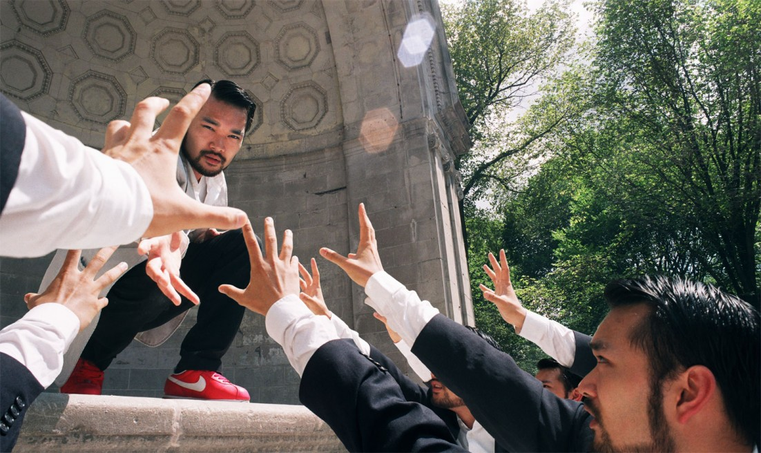An Asian man on a domed stone stage in a white suit with Asian men in black suits reaching from below.