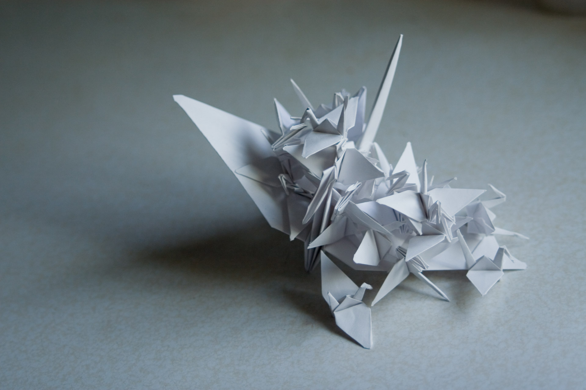 Large and small white paper cranes on a counter top.