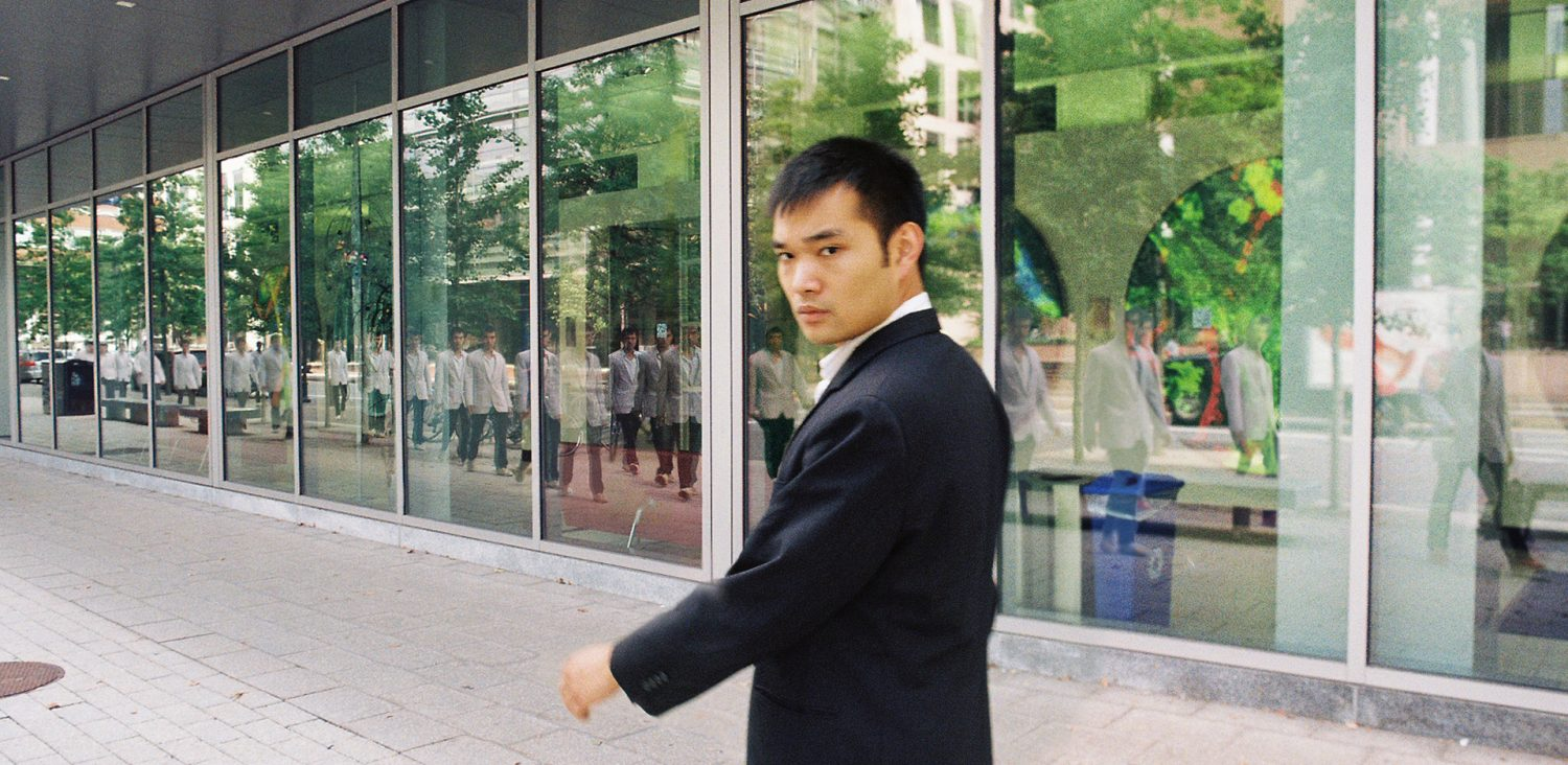 An Asian man in a dark suit looking back into the camera while walking down a street. A group of the Asian man in white, walking the other way in the reflection.