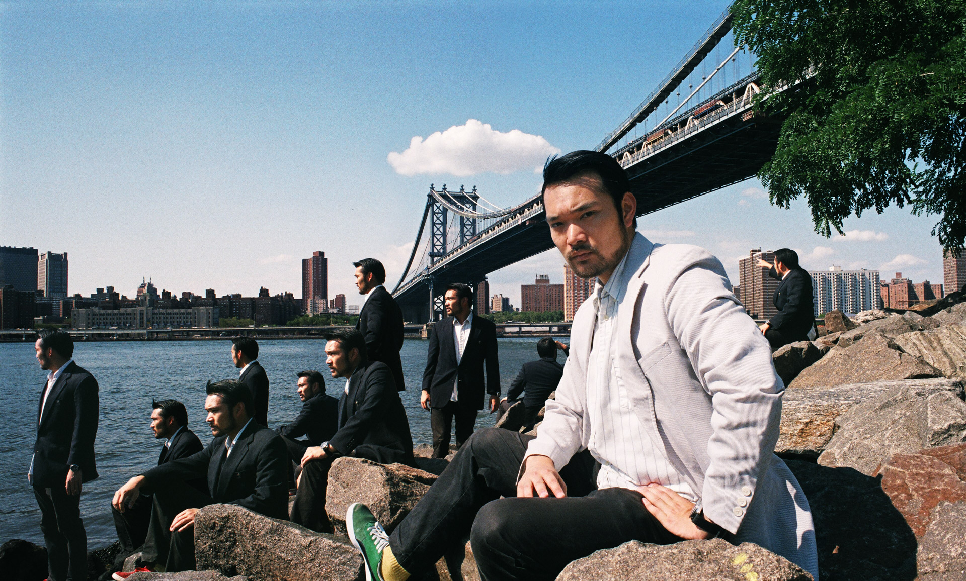 A group of Asian men in Dark suits on the rocks by a river, same asian in a white suit looking into the camera.