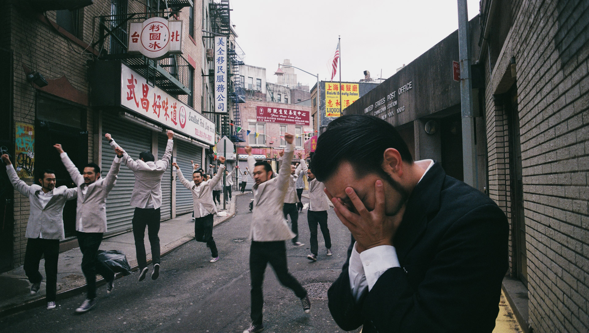 A group of asians in white suits celebrating, same asian in a dark suit hiding his face in shame.