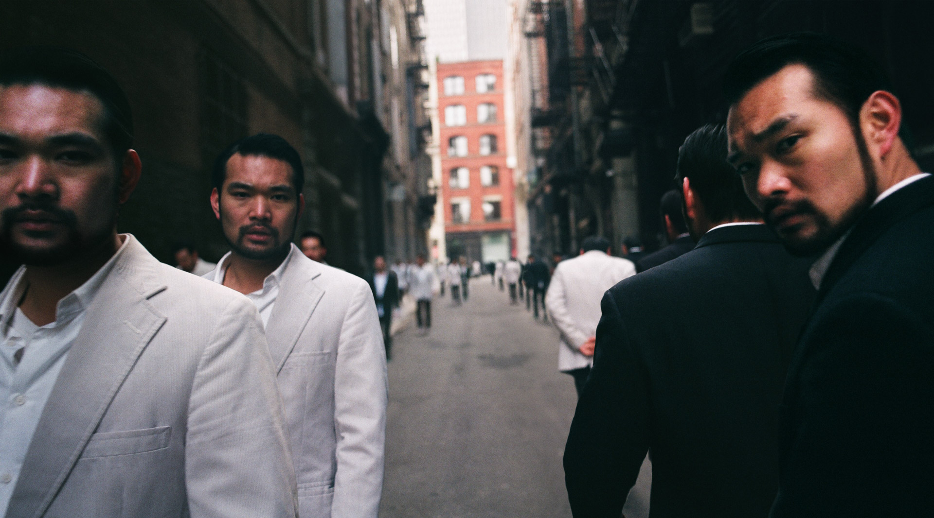 a group of asians in white and black suits walking towards and away from the camera.