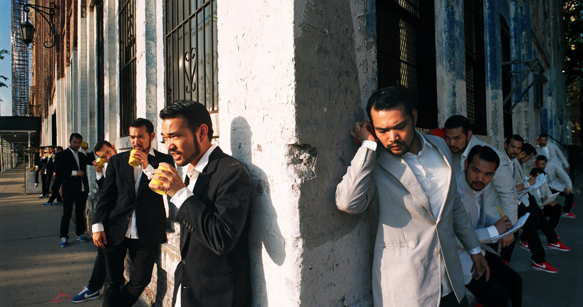 A group of asians in dark suits on a corner talking on the phone, same group of asians in white around the corner writing down what they are saying.