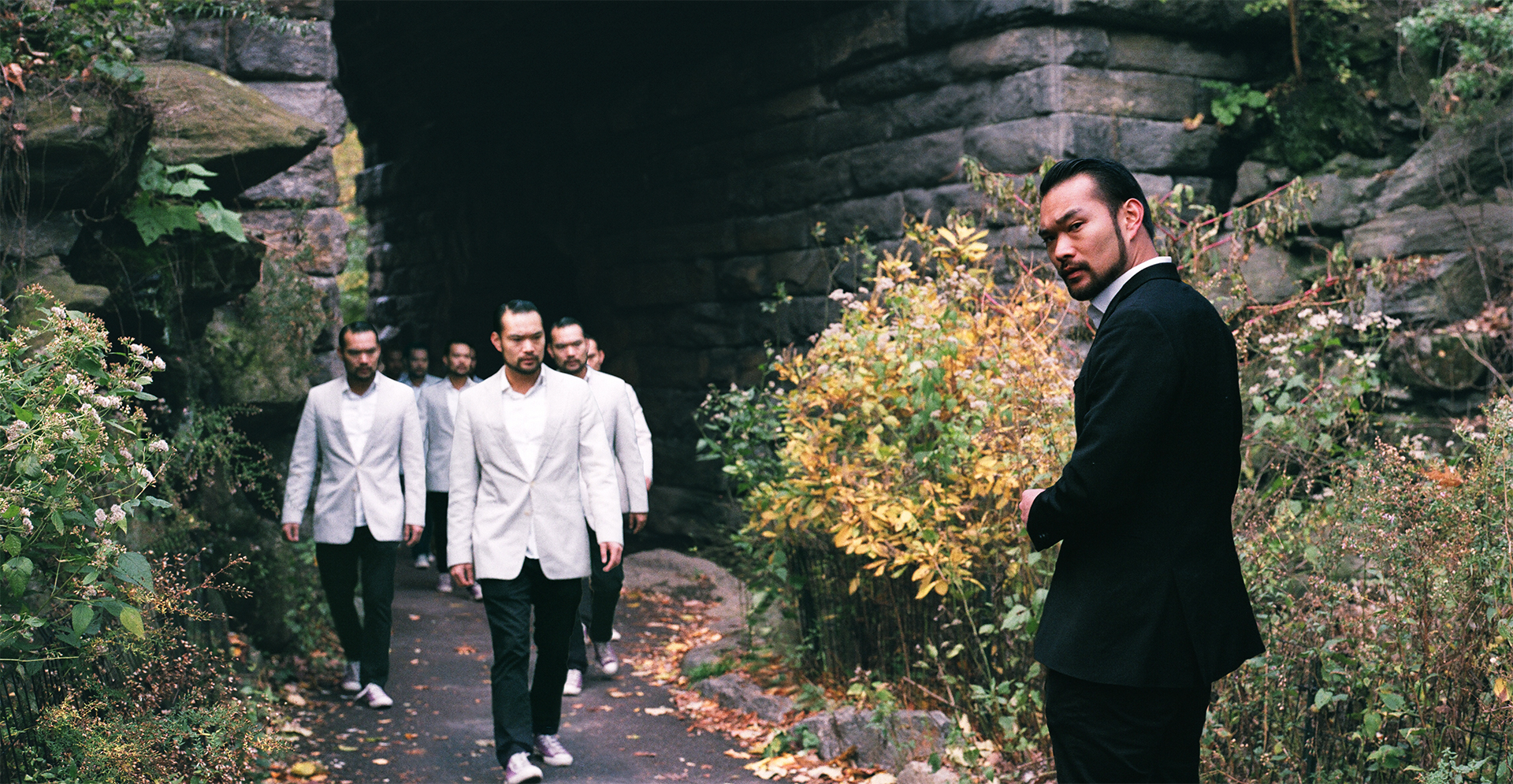A group of Asian men in white walking under a bridge, towards an Asian man in a black suit.