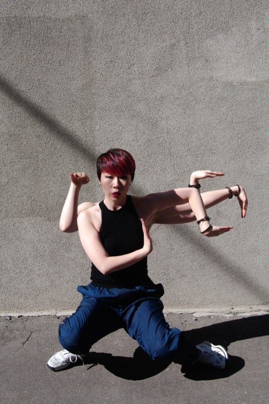 Popping Monster - Sun Kim, Crane Strike. Sun Kim dancing in DUMBO Brooklyn with 5 arms, looking into the camera.