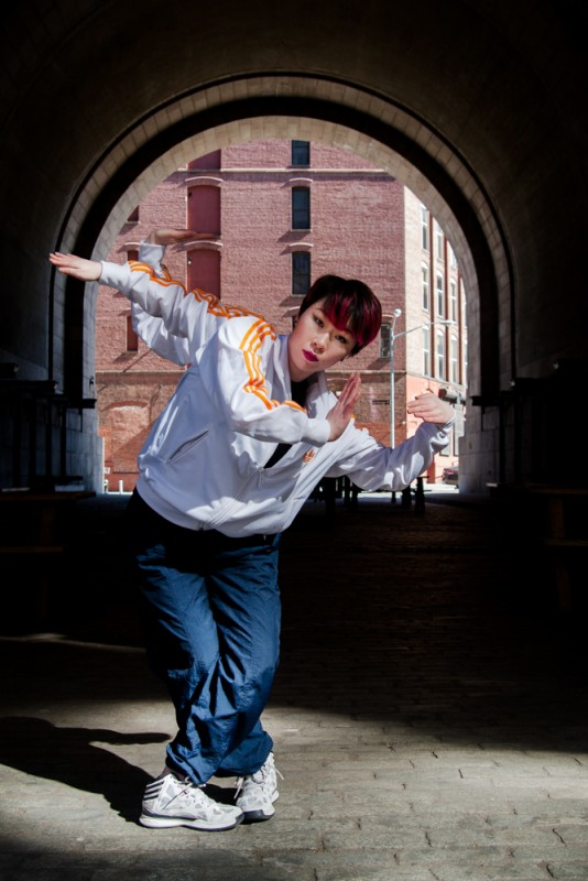 Popping Monster - Sun Kim, Cross Chop. Sun Kim dancing in DUMBO Brooklyn with 4 arms, looking into the camera.