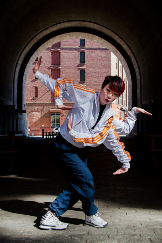 Popping Monster - Sun Kim, Falling Strike. Sun Kim dancing in DUMBO Brooklyn with 5 arms, looking into the camera.