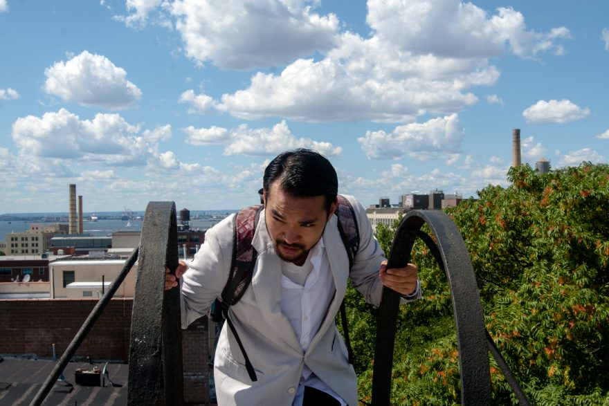 Shinobi No Kame BTS - An Asian man in a white suit climbing down the side of a fire escape.